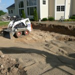 Order Traffic Bond (usually 1/4″ with fines) and fill in the hole you just dug.  This is the same material that gets compacted under your concrete flat work.