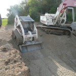 Bobcat is used to Move the TB Around the Hole as the Excavator Drops the Stone in the Hole.
